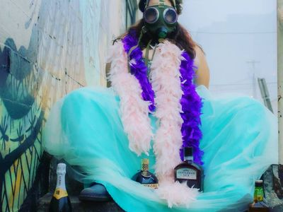 """Portland Queer Comedy Festival Founder Belinda Carroll, pictured here donning a gas mask and feather boas, will co-host the <a href=""""https://everout.com/portland-mercury/events/international-coming-out-day-comedy-extravaganza/e36902/"""">International Coming Out Day Comedy Extravaganza</a> this Sunday on YouTube and XRAY.FM."""