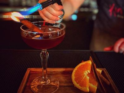 """<a href=""""https://everout.com/stranger-seattle/locations/kin-len-thai-night-bites/l13855/"""">Kin Len</a>'s """"A Prayer Before Dawn"""" cocktail is garnished with a freshly torched cinnamon stick."""