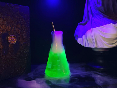"""The spooky new cocktail bar <a href=""""https://everout.com/portland/locations/ravens-manor/l40642/"""">Raven's Manor</a> offers """"eerie elixirs,"""" like the glowing green """"Dr. Raven's Reserve"""": coconut rum, pineapple juice, Midori, and spritzer, served in an Erlenmeyer flask."""